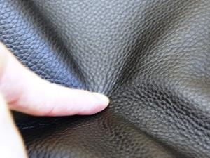 本革の表面を指で押しています。
